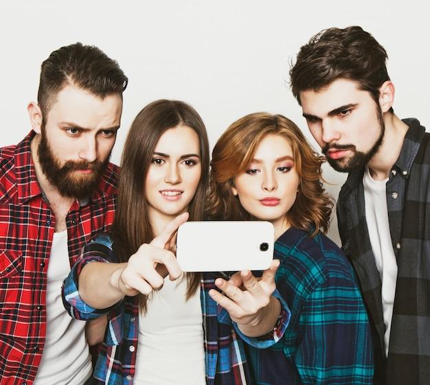教育、技術、人々の概念:ホワイトスペースでスマートフォンでselfieを取っている学生のグループ。特別なおしゃれな調子を整える。