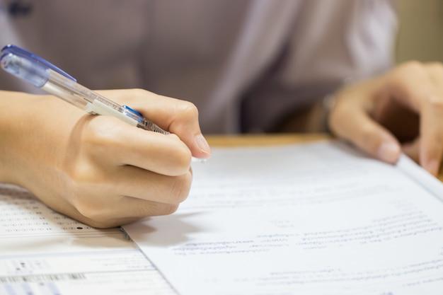 教育テストの概念:男の手の高校、試験のための鉛筆を保持している大学生