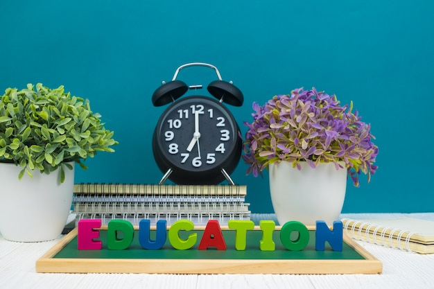 Education text and green chalkboard with pile of notebook paper
