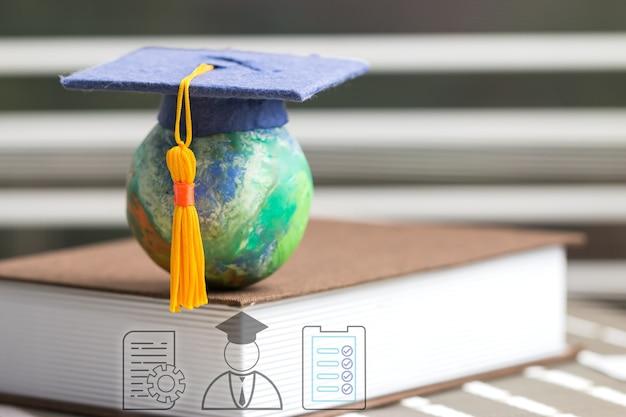 Образование, чтобы учиться учиться в мире. дипломированный студент, обучающийся за границей, международная идея. шляпа магистра на верхней книге глобуса. концепция аспирантуры для длительного дистанционного обучения в любом месте в любое время