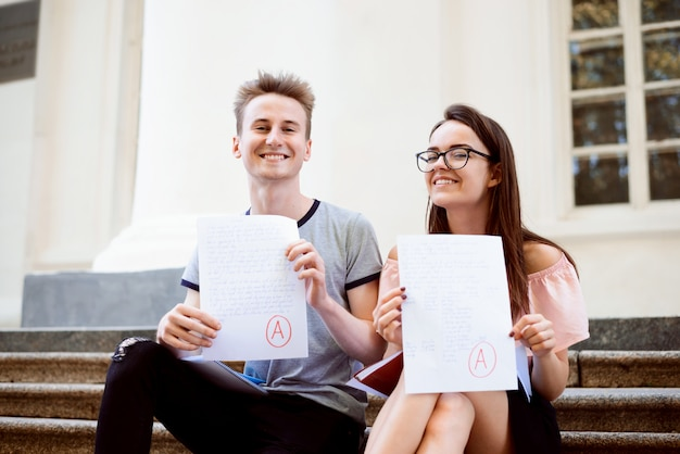 Education, university concept. two teenagers or students holding test or exam with grade a