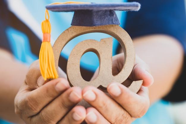 Образовательный университет онлайн-обучения за рубежом образовательная концепция: выпускной колпачок на символ адреса электронной почты в руке студента. международная школа idea communication может учиться с помощью интернет-технологий