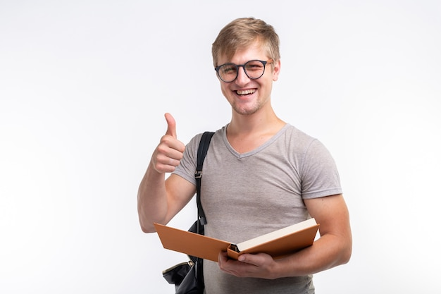 Концепция образования, университета, людей - студент с книгой показывает нам большой палец вверх, потому что ему нравится