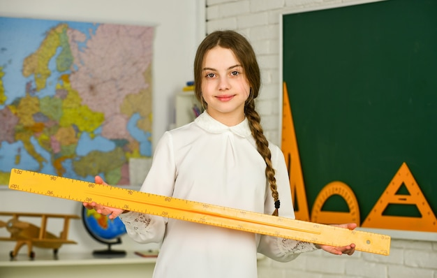 Education and university. school girl hold ruler. instrument of measurement. different school elements. stationery in autumn school time. back to school. education in college. mired in geometry.