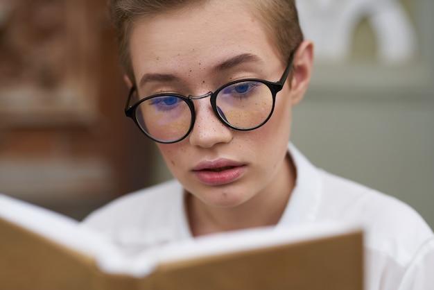 眼鏡をかけた教育女性女子学生ハンドモデルのクローズアップで研究所の本の近く