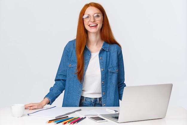 教育、仕事、フリーランスのコンセプト。魅力的なカリスマ的な赤毛の女性デジタル遊牧民、リモートで作業するデザイナー、デザインプロジェクトの作成、ラップトップ、色鉛筆でテーブルの近くに立っています。
