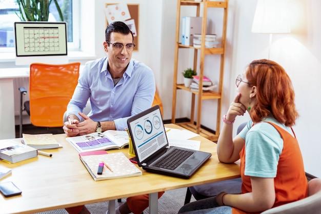 교육 활동. 그녀의 선생님을 보면서 노트북 화면 앞에 앉아 긍정적 인 젊은 여자
