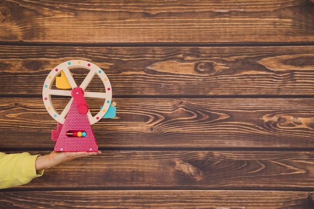Развивающие детские игрушки из дерева. игрушка в виде разноцветной мельницы под рукой неузнаваемого человека на деревянном фоне.