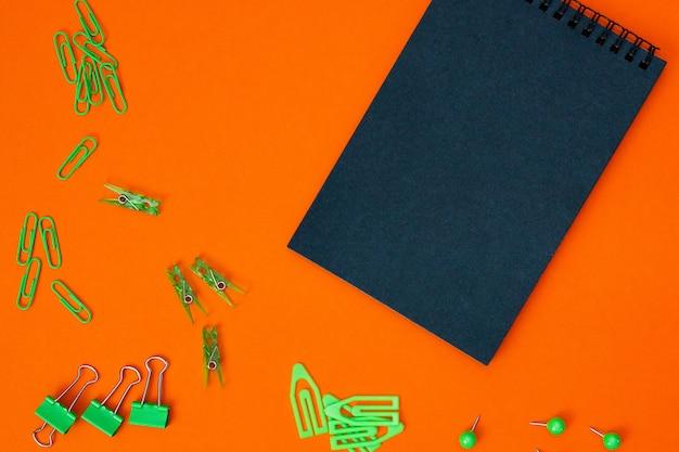 Учебная композиция, канцтовары. зеленые канцтовары и черный блокнот на черном фоне
