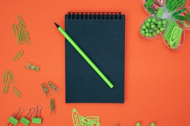Educational composition, stationery. green stationery and black notebook on black