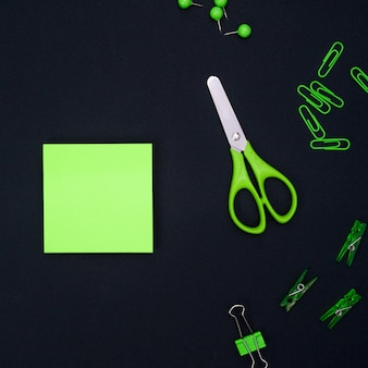 Educational composition, stationery. green stationery and green notebook on a black background. flat lay, top view, copyspace.