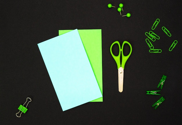 Educational composition, stationery. green stationery and green notebook on black