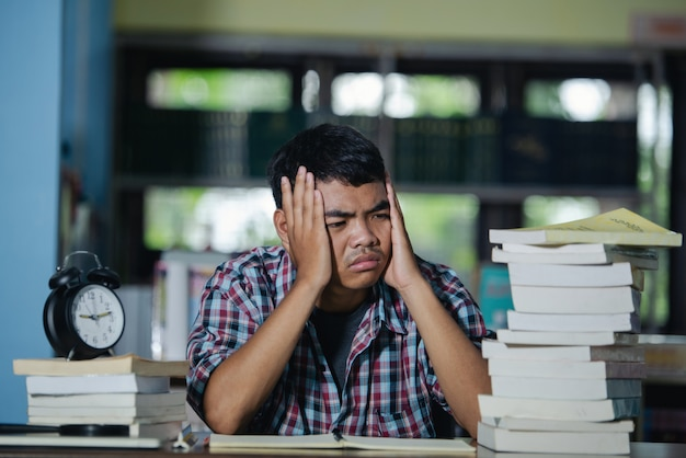 Образовательный концепт: уставший студент в библиотеке