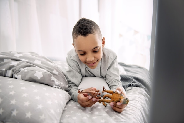 Educational game. appealing afro american boy posing on bed while playing with dinosaurs toys