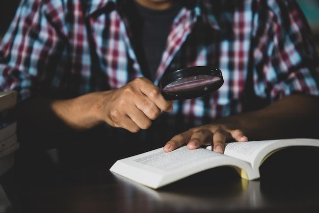 教育テーマ:クローズアップ-虫眼鏡を通して本を見る学生