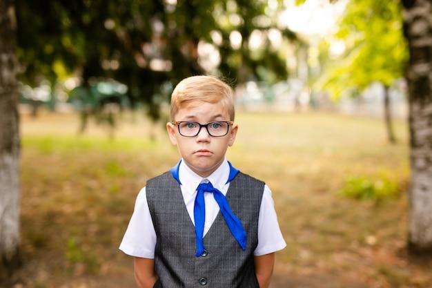 교육 테마 : 큰 검은 안경와 파란색 넥타이와 모범생의 초상화. 학교 뒤뜰, 수업 시작
