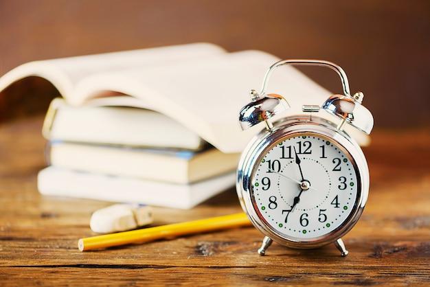 教育のコンセプトです。目覚まし時計、木製のテーブル、セレクティブフォーカスの本