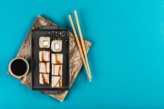 うなぎとチーズは、水色の背景に箸と醤油を添えた皿の上で転がります。コピースペースのある上面図。