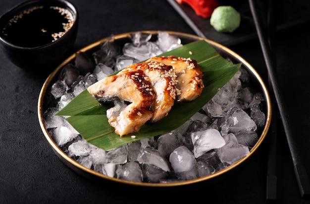 Сашими из угря на льду в черной тарелке