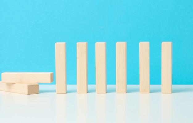 青い背景に対するドミノの効果。チームワークの概念、外部ソースの影響の結果を防ぐ能力