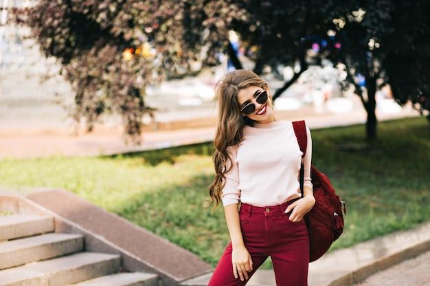 Эффектная девушка с длинными вьющимися волосами в бордовых штанах позирует на улице в городе.