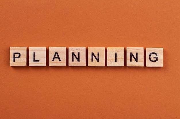 プロジェクトの成功のための効果的な計画。オレンジ色の背景に分離された木製の立方体の文字。