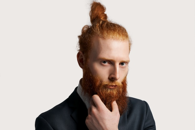 Effective and talented businessman with red hair with strong sight and hold his beard by hand
