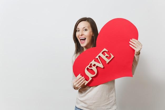 큰 붉은 마음을 들고 효과적인 젊은 웃는 여자, 흰색 바탕에 나무 단어 사랑. 광고 공간을 복사합니다. 텍스트에 대 한 장소. 성 발렌타인 데이 또는 국제 여성의 날 개념.