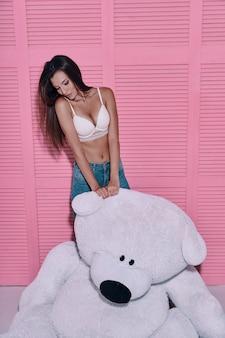 楽な美しさ。ピンクの背景に立っている間大きなおもちゃのクマと遊ぶ魅力的な若い女性