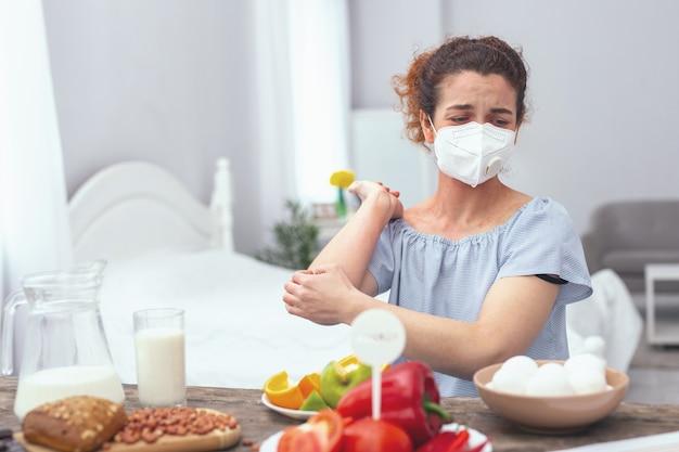 卵アレルギー。製品の匂いで彼女に影響を与える重度の卵アレルギーの症状を示す呼吸マスクを身に着けている若い女性