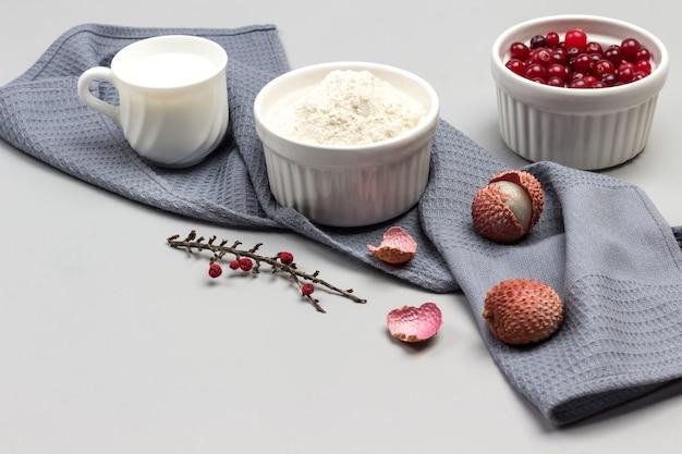 小麦粉の卵とボウル、牛乳のカップ、灰色のナプキンにライチの果実。クランベリーのボウル。上面図。