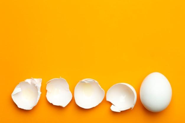 色付きの空の背景に卵と卵殻。最小限の食品のコンセプト、創作料理。
