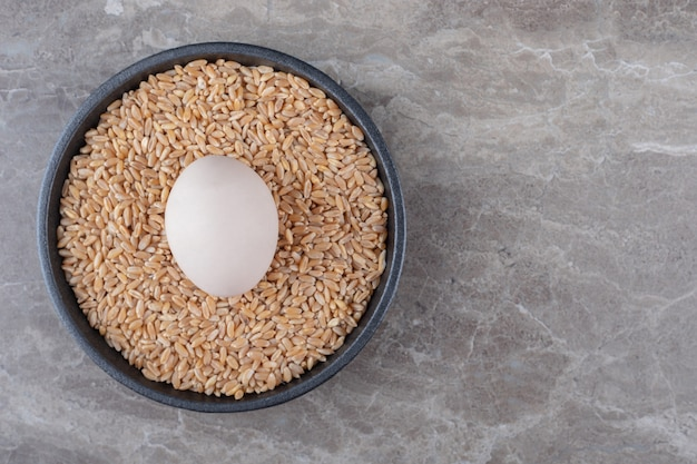 Яйцо и куча ячменя на черной тарелке.