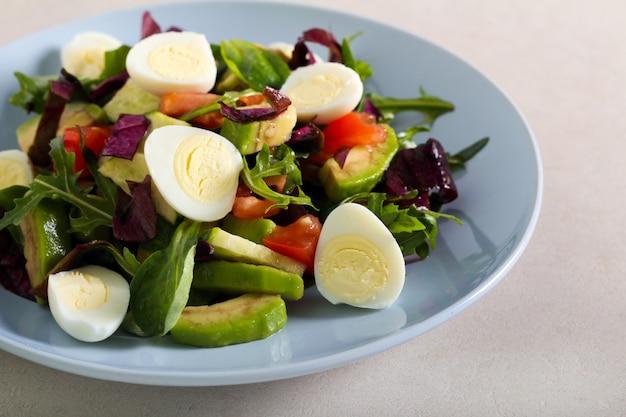 Салат из яиц, авокадо, огурцов и помидоров на тарелке