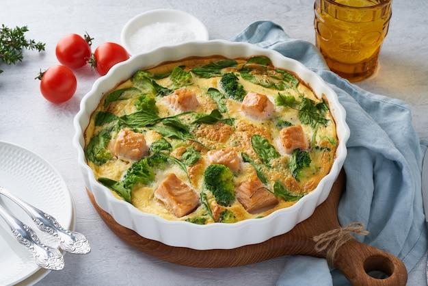 卵ベースのフリッタータ、サーモン、ブロッコリー、ほうれん草のオムレツ。卵入りのクラストレスキッシュ