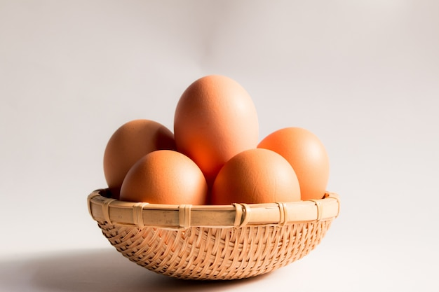 Egg in basket wicker on white background,duck eggs in baskets .
