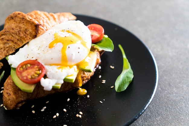 Egg benedict with avocado, tomatoes and salad
