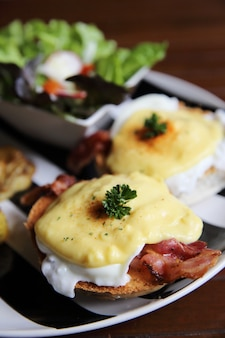 Egg benedict with bacon and potato on wood background