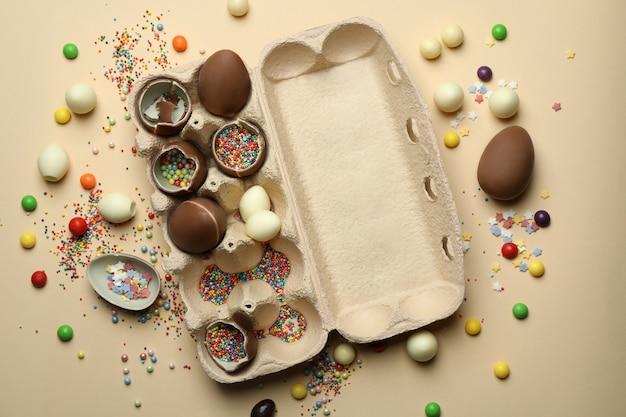 베이지 색 벽에 뿌리와 초콜릿 달걀과 달걀 상자