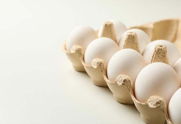 Коробка для яиц со свежими яйцами на белом фоне