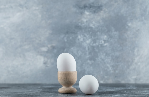 Egg cup and eggs on grey table.