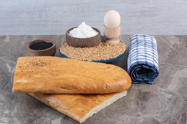 검은 참깨 그릇, 수건 롤, 대리석 배경에 빵 덩어리 옆 플래터에 달걀 컵, 밀가루 그릇 및 밀 더미. 고품질 사진