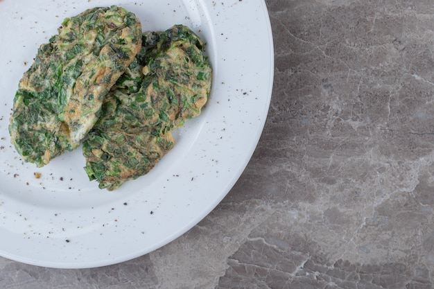 Egg cutlet with greens on white plate.