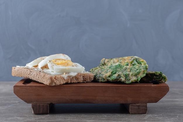 Cotolette di uova con verdure e pane tostato su tavola di legno.