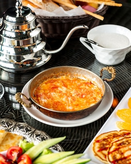 Egg dish with tomato served in turkish copper pan