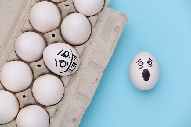 파란색 배경에 계란 트레이에 의료 마스크에 계란 얼굴. 코로나 19 감염병 세계적 유행. 평면도
