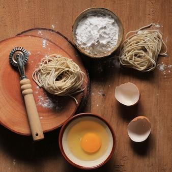 木の板に卵、小麦粉、生のアジアンヌードル