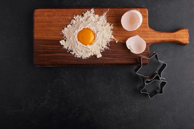 Uova e farina mescolate tra loro su tavola di legno, vista dall'alto.
