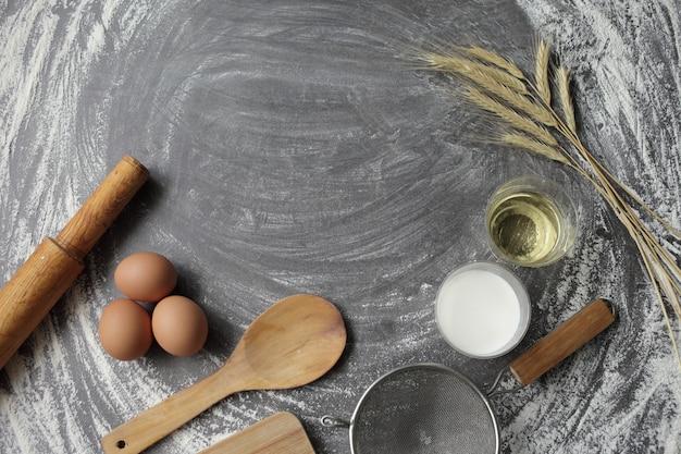 Яйцо, мука, оливковое масло, молоко, колосья пшеницы, кухонный инвентарь на сером фоне стола.