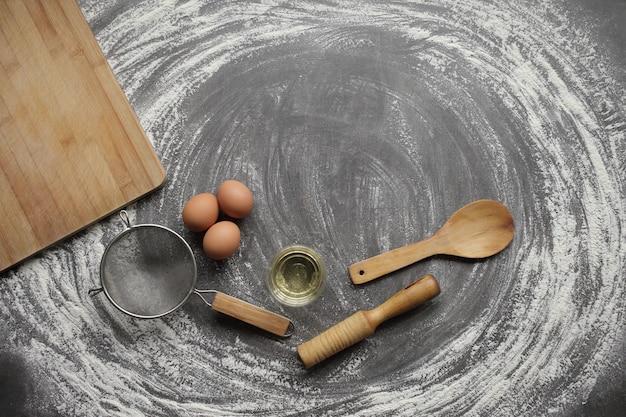 계란, 밀가루, 올리브 오일, 우유, 밀 귀, 회색 테이블에 주방 도구